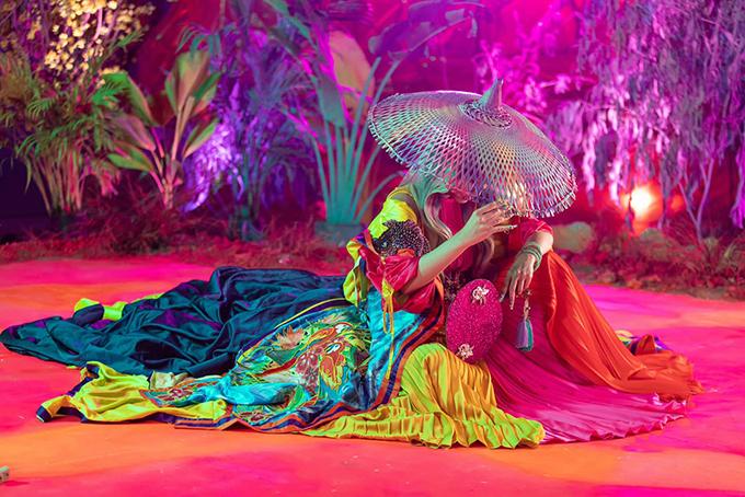 Set đồ chủ đạo của MV được mix khá độc đáo với 3 mẫu đầm xếp ly của nhà mốt Adrian Anh Tuấn. Stylít Hoàng Ku chọn thêm áo khoác sắc màu nhiệt đới của Iris Trịnh và nón rộng vành của Ngô Mạn Đông Đông tạo nên tổng thể hoàn hảo.