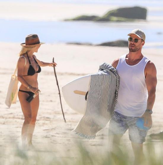 Chris Hemsworth ôm cây lướt ván cùng bà xã Elsa Pataky ra bãi biển gần nhà hôm 5/4. Khu vực này cách biệt với xung quanh nên luôn vắng vẻ.