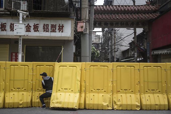 Một người chui qua hàng rào tạm thời được dựng lên để kiểm soát lối ra vào khu dân cư ở Vũ Hán hôn 31/3. Ảnh: Bloomberg.