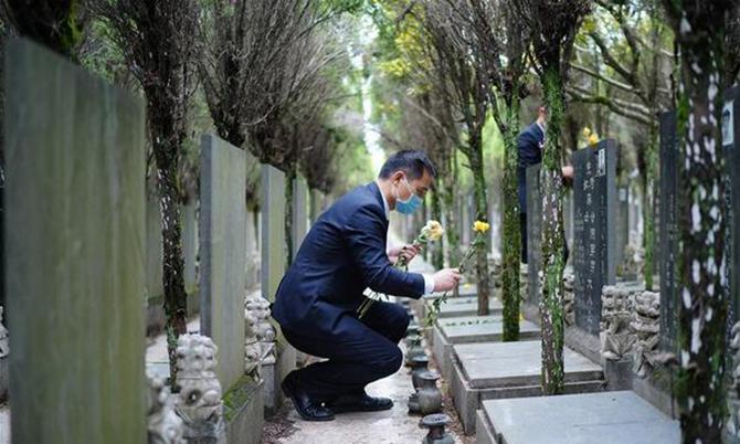 Một nhân viên nhà tang lễ đặt hoa lên mộ người đã khuất ở một nghĩa trang tại Thượng Hải vào lễ Thanh minh cuối tuần trước. Ảnh: Xinhua.