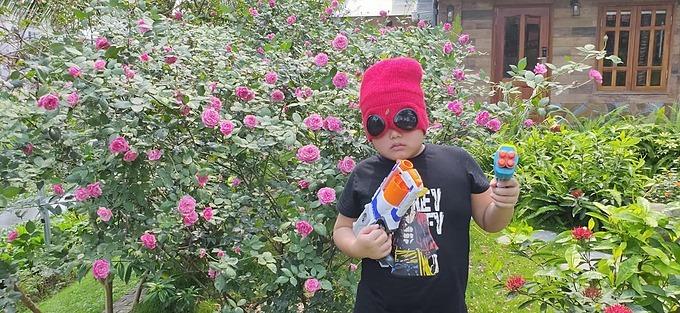 Bi béo nhà Xuân Bắc nhờ bố chụp ảnh với vũ khí trong vườn nhà để thách đấu với quân địch là virus corona.