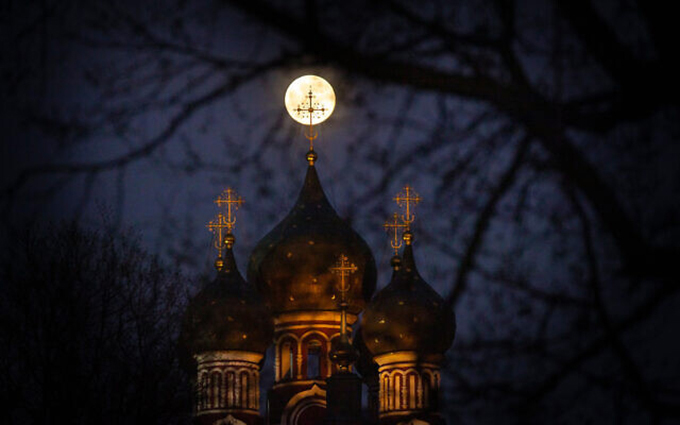 The supermoon rises behind an illuminated cross from a Christian Orthodox church in Moscow, Russia, April 7, 2020