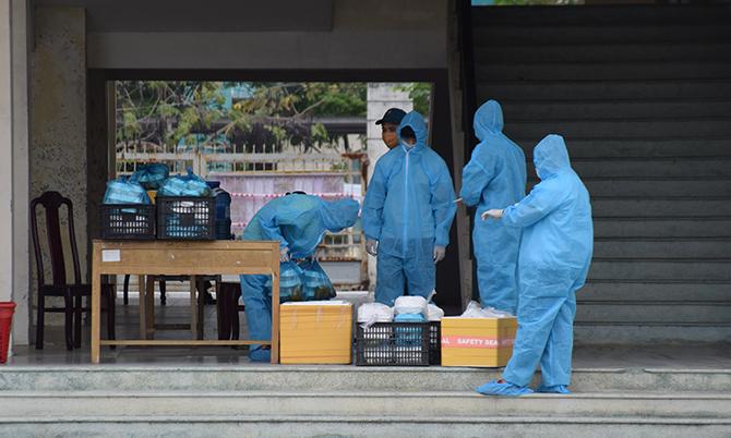 Lực lượng chức năng đưa cơm cho những người đang cách ly tập trun tại Trường Cao đẳng Y tế Quảng Nam, sáng 9/4. Ảnh: Sơn Thủy.