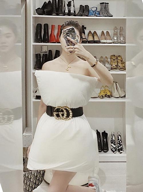 Jolie Nguyễn chọn dây dưng Gucci, túi xách Dior để mix cùng gối lông ngỗng trắng.