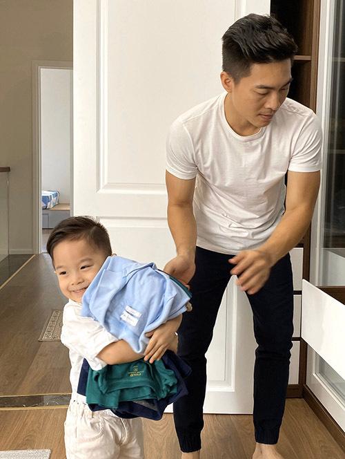 Bé Bắp thu gom quần áo cất vào tủ. Nhờ bận rộn với nhiều hoạt động trong nhà nên nhóc tỳ luôn vui vẻ không đòi ra ngoài chơi.