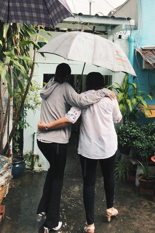 Trời Sài Gòn đổ mưa lớn chiều 9/4 nhưng hai mẹ con Khánh Vân cùng che ô cố gắng hoàn tất việc trao quà.