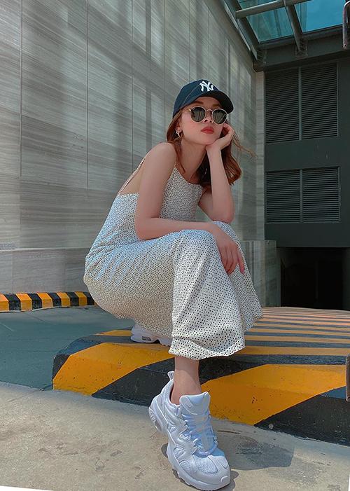Phong cách nữ tính và không kém phần trẻ trung của Yến Trang với cách phối váy hai dây cùng giày đế thô, mũ lưỡi trai.