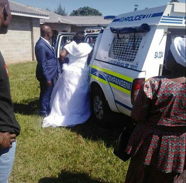 Cặp vợ chồng mới cưới bị mời lên xe cảnh sát ở tỉnh KwaZulu Natal, Nam Phi hôm 6/4. Ảnh: Twitter.