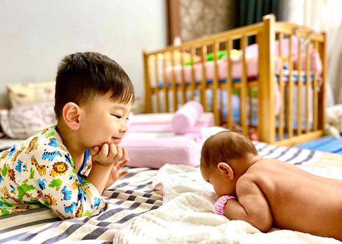 Cậu nhóc gần 4 tuổi cổ vũ em tập ngóc đầu dậy khi được đặt nằm sấp trên giường.