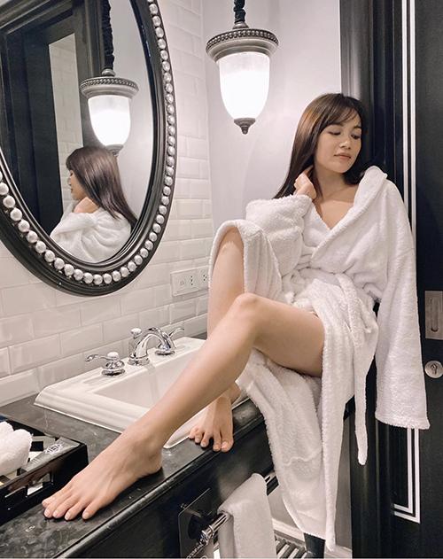 Sĩ Thanh khéo kéo dài đôi chân khi chụp ảnh cùng áo choàng thiết kế trên sợi cotton thấm hút nước nhanh chóng.