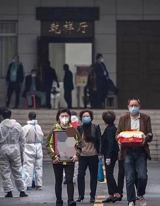 Một gia đình ở thành phố Vũ Hán đi nhận tro cốt người thân chết vì Covid-19 tháng trước. Ảnh: Weibo.