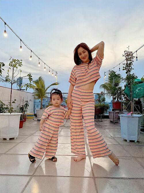 Con gái bắt chước Khánh Thi tạo dáng pose hình trên sân thượng.