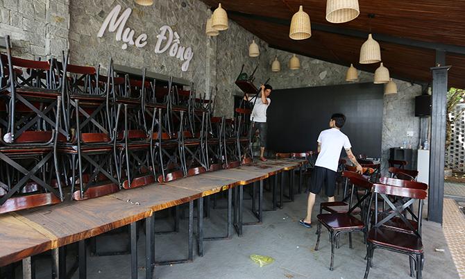 Nhân viên một quá trên đường Bạch Đằng, TP Tam Kỳ dọn dẹp bàn ghế sau thời gian đóng cửa, sáng 23/4. Ảnh: Sơn Thủy.