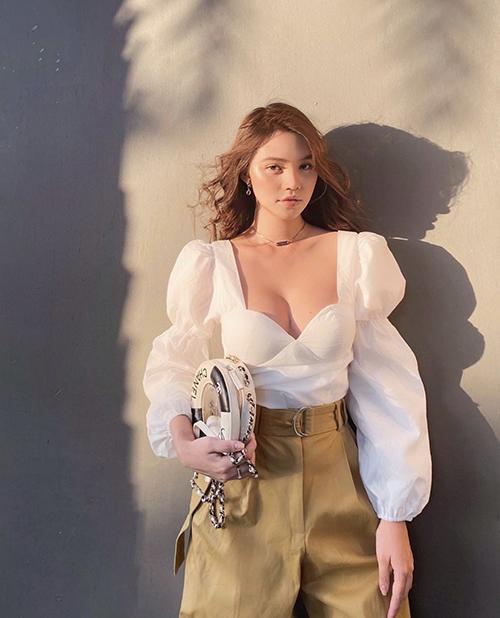 Túi đeo chéo hình phao bơi của Chanel được Jolie Nguyễn mix cùng áo tay bồng, quần lưng cao khi chụp ảnh tại nhà.