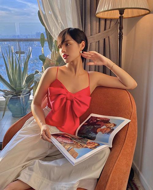 Cùng với áo hai dây vải thun ôm sát body, Khánh Linh còn chọn thêm kiểu áo trang trí nơ bướm to bản để phối cùng quần ống suông.