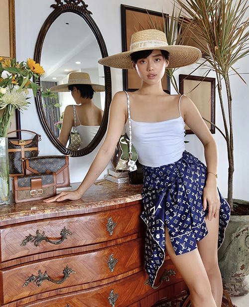 Kiểu áo hai dây quen thuộc ngày hè được Khánh Linh biến tấu cùng pyjama. Mẫu áo mặc ở nhà được fashionista sử dụng như váy vạt quấn để thể hiện sự sáng tạo và phá cách.