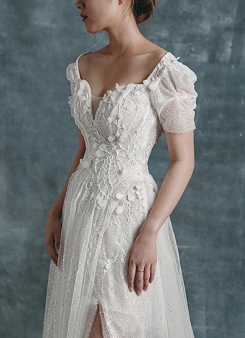Phần tay váy có điểm nhún, còn ngực áo là cổ vuông cách điệu giúp cô dâu khoe khéo nét gợi cảm.