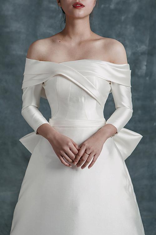 Cổ áo được tạo hình dựa trên cảm hứng từ nghệ thuật xếp giấy origami. Vẻ đẹp của váy tối giản chính là ở chất liệu, thiết kế thay vì hoạ tiết như váy cưới thông thường.