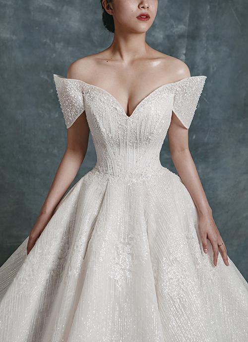 Bộ đầm được đính kết các hạt ngọc, hoạ tiết nổi giúp bắt sáng tự nhiên. Phần tay váy được dựng phom cầu kỳ, thể hiện tinh thần nữ quyền.