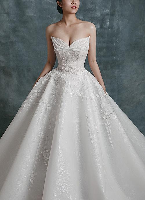 Hạt ngọc được điểm xuyết dọc thân, còn tà váy được trang trí bởi hoạ tiết hoa ren nhẹ nhàng.