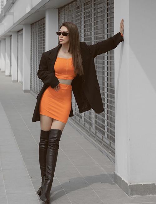 Khổng Tú Quỳnh chọn màu cam để giúp mình nổi bật trên phố. Các phụ kiện tôn nét cá tính như kính mini, bốt da cao cổ được ca sĩ chọn làm điểm nhấn.