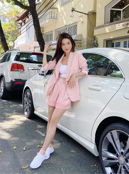 Sĩ Thanh khoe vòng eo thon gọn và phong cách trẻ trung với suit hồng phấn. Cô chọn áo hở eo và giày thể thao tông trắng để mix màu hài hòa.