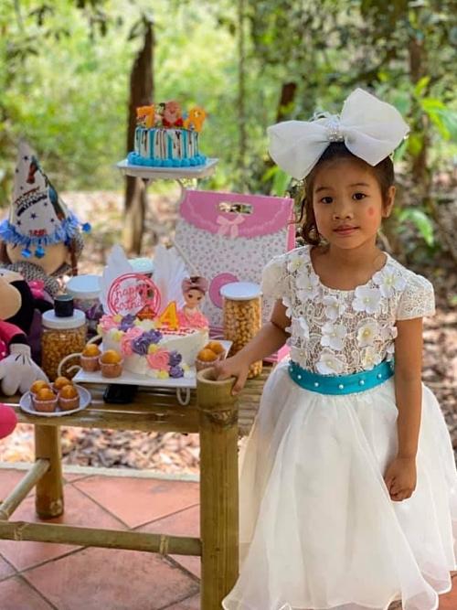 Con gái Thanh Thư 'xúng xính' trong bộ váy công chúa màu trắng. Các món quà mừng tuổi bé được đặt trên bộ bàn trà bằng tre do chính Kiều Trinh đóng.