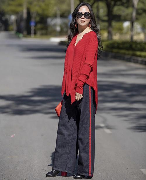 Tông đỏ được chọn là điểm nhấn xuyên suốt cho set đồ dạo phố gồm áo free size, quần suông, clutch và giày móng ngựa, đế đỏ.