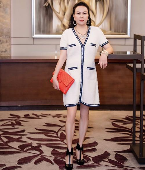 Nữ doanh nhân chọn clutch da dê màu đỏ cam để hoàn thiện nguyên cây hàng hiệu gồm váy, vòng cổ, hoa tai của Chanel.