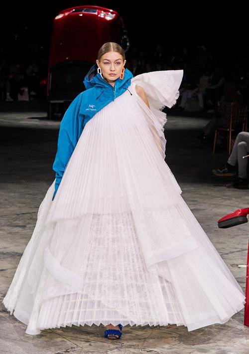 Xuất hiện trên sàn diễn Off-White cùng mẹ và em gái Bella hôm 27/2, Gigi Hadid đảm nhận vai trò vedette. Cô trình diễn thiết kế độc đáo pha trộn giữa áo khoác gió màu xanh bắt mắt và đầm trắng xếp ly dáng chữ A xoè rộng.