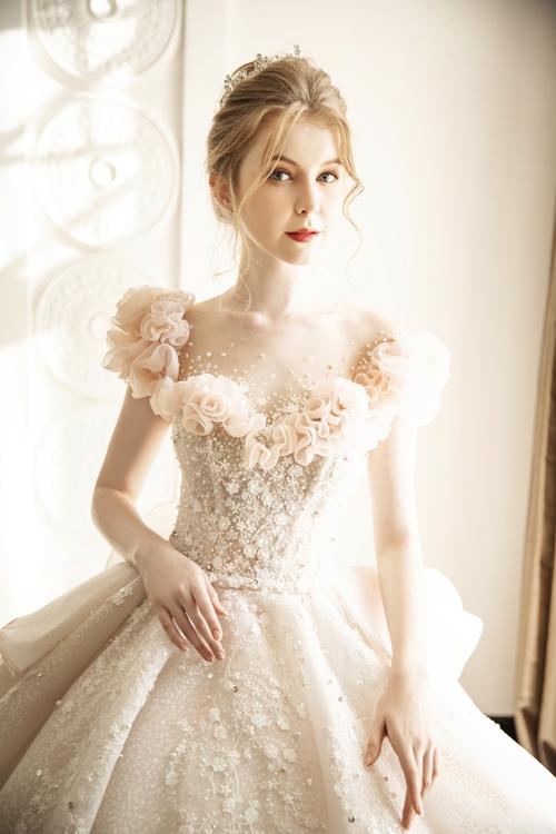 Sức cuốn hút của bộ cánh hồng pastel tiếp theo nằm ở họa tiết hoa hồng xuyên suốt, điểm dọc thân. Loài hoa này được chọn lựa là biểu tượng tình yêu, giúp cô dâu gửi đi thông điệp về tình cảm hạnh phúc trong ngày đại hỷ. Những khối hoa 3D nở rộ trên phần vai áo hút ánh nhìn. Điểm xuyết dọc thân áo là những đóa hoa nhỏ, đá pha lê giúp phù phép cô dâu thành công chúa cổ tích ở lễ đường đám cưới.