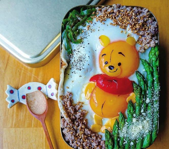 Gấu Pooh cũng được làm từ 2 quả trứng ốp, nổi bật phần đầu và bụng bự của chú gấu đáng yêu. Hộp cơm được trang trí thêm bằng măng tây, ớt chuông, ăn kèm gạo lứt bổ dưỡng.