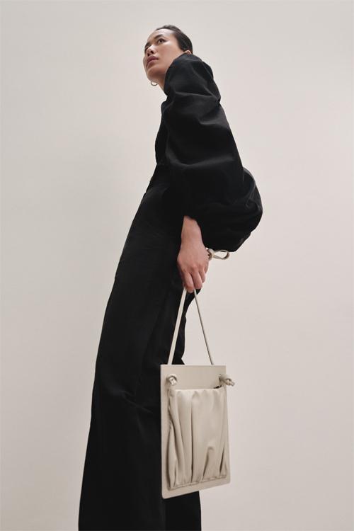 , trong mùa mốt Xuân Hè 2020, NTK Lâm Gia Khang tiếp tục mang đến chiếc túi Ionic – từng xuất hiện năm 2015 song được làm mới lại. Với dáng dấp mảnh dẻ đầy nữ tính cùng bề mặt cứng trắng mô phỏng lại đế cột và hai nút thắt thể hiện họa tiết xoắn ốc đặc trưng trên cột Ionic