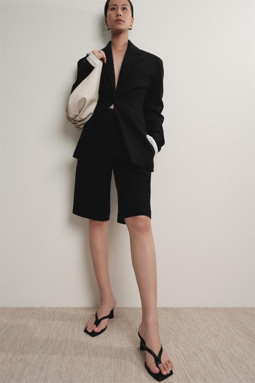 Blazer cho mùa mới được biến tấu đôi chút ở phần eo bằng kỹ thuật drape, tôn vinh đường nét mềm mại vốn có của phụ nữ. Trang phục kết hợp một cách đầy phá cách với quần lửng và giày sandal mô phỏng phong cách Hy Lạp cổ.