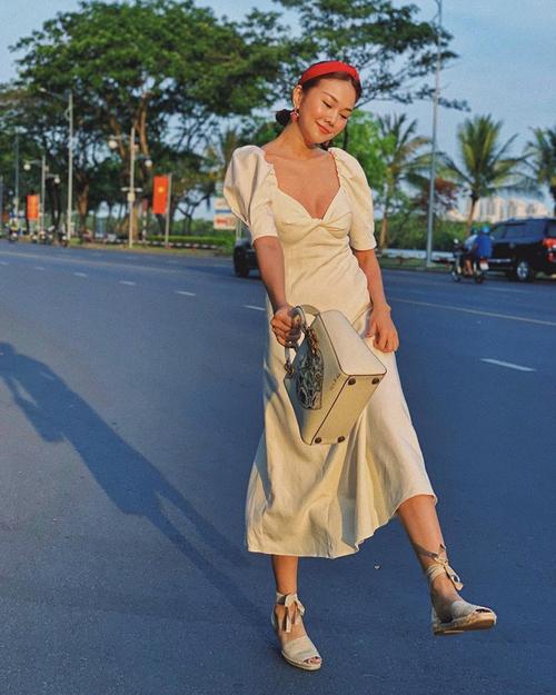 Song song với những xu hướng sắc màu hot trned 2020, tông trắng thanh lịch vẫn được Thanh Hằng và sao Việt ưa chuộng. Kiểu váy tay bồng, cắt cúp phần ngực ấn tượng được siêu mẫu mix đồng điệu cùng sandal cột dây, túi Dior.