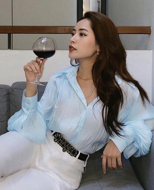 Sơ mi lụa bóng hợp xu hướng mới với tông xanh thiên thanh được Chi Pu sử dụng ăn ý cùng jeans trắng.