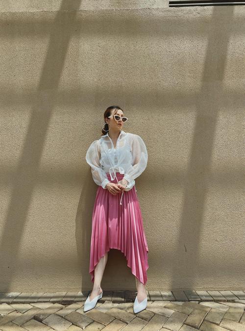 Sơ mi trắng trong suốt được Yến Nhi sử dụng một cách tinh tế cùng áo hai dây tiệp màu và chân váy xếp ly gam hồng đậm chất nữ tính.