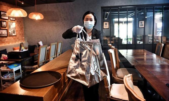 Một nhân viênSilver Voyage Club chuẩn bị giao thức ăn đến khách hàng VIP. Ảnh: AFP.