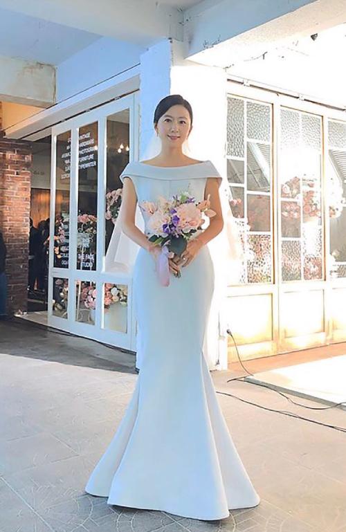 Cận cảnh mẫu váy cưới của nữ chính phim Thế giới hôn nhân. Bộ đầm mang phom dáng đuôi cá, có độ xòe nhẹ từ đầu gối, giúp tôn dáng ngọc của người diện. Váy được kết hợp cùng voan ngắn không họa tiết. Nữ diễn viên Kim Hee Ae thủ vai Sun Woo chọn kiểu tóc búi đơn giản, chải ngôi lệch khi diện váy phom dáng cổ điển. Ảnh: Instagram