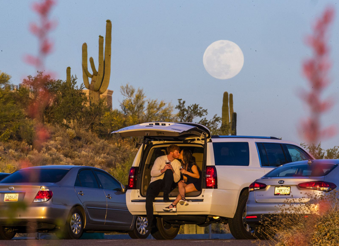 Clint and Kaylee Frazier enjoy the sunset as the moon rises over Fountain Hill, Arizona, on Wednesday, May 6. The flower moon, like many of the monthly moon names, can be attributed to how Native Americans tracked the seasons, according to the Old Farmers Almanac.