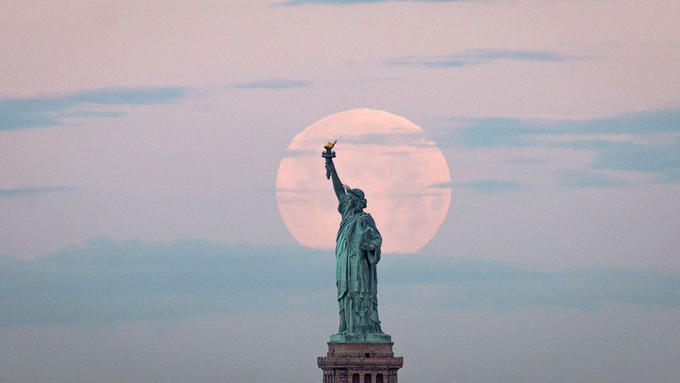 The moon is seen behind the Statue of Liberty in New York.