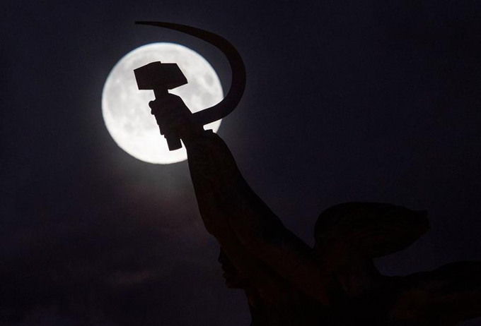 The super flower moon is seen behind the sculpture of Worker and Kolkhoz Woman in Moscow, Russia.