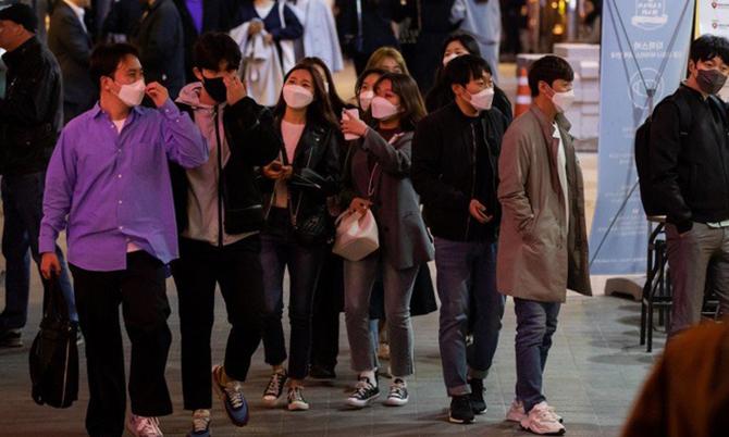 Nhiều người đeo khẩu trang đi bộ trên con phố ở quậnItaewon, địa điểm vui chơi, giải trí với nhiều quán bar ở Seoul. Ảnh: Bloomberg.