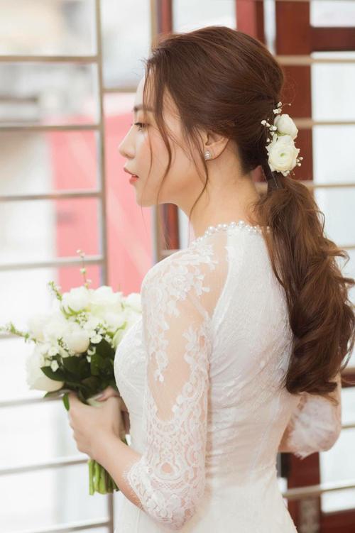 NTK đính kết hạt bẹt, hạt pha lê dọc thân áo để tạo độ bắt sáng tự nhiên. Việc sử dụng lớp ren mỏng cho tay áo giúp tôn vinh nét đẹp dịu dàng, gợi cảm của cô dâu. Cổ áo được đính ngọc trai để tạo điểm nhấn.