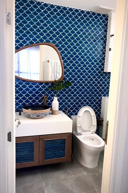 Nhà vệ sinh có tường hình vảy cá, gương có hình khối cách điệu.