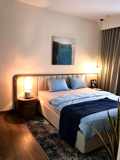 Phòng ngủ chính của gia chủ mang lối tối giản và được trang trí với tranh cùng tông xanh chủ đạo.