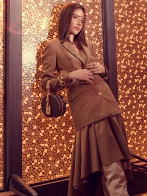 Nam Anh diện vest màu nâu trầm, kết hợp cùng chân váy mullet và giày ống lạ mắt. Cô phối thêm chiếc túi tròn Louis Vuitton đồng màu, tạo sự hài hoà cho tổng thể.