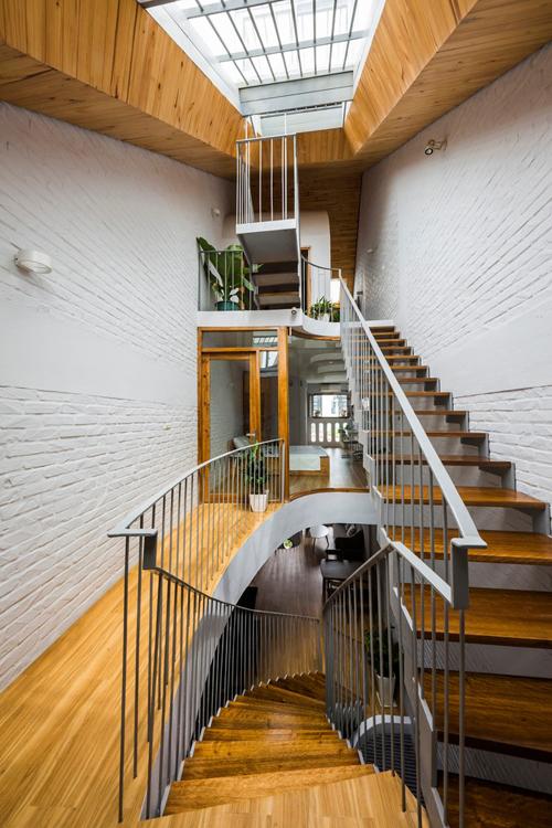 Những bức tường với đường uốn cong và cầu thang tối ưu không gian đất không vương vức, tạo dựng sự mềm mại cho nhà ống đô thị.