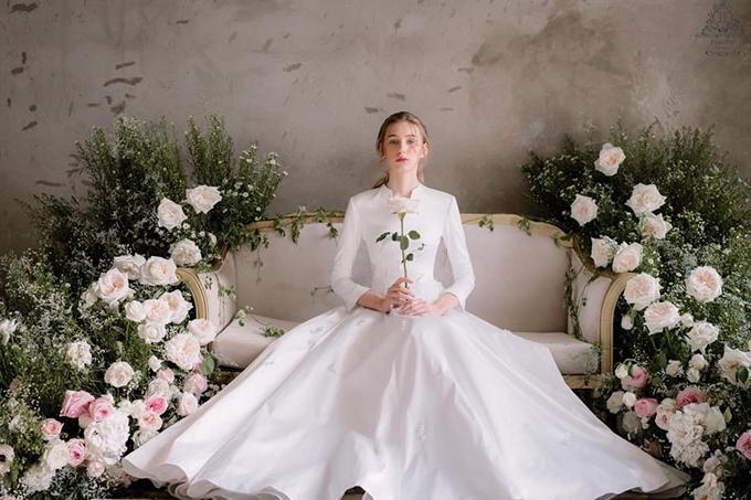 Một lựa chọn khác cho cô dâu yêu thích phong cách váy xoè của Nam Phương Hoàng hậu là váy chữ A được biến tấu với tay dài, cổ V. Nét đẹp của váy cưới tối giản nằm ở chất liệu, các kỹ thuật xử lý phom dáng, mang đến vẻ đẹp vượt thời gian.
