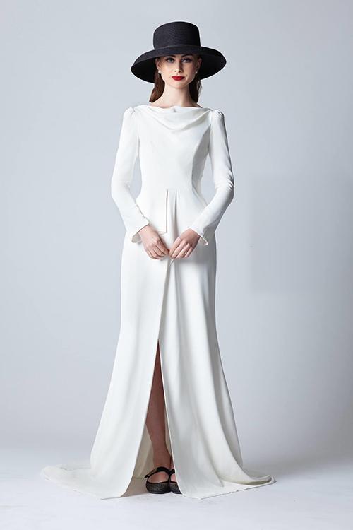 Bộ đầm xoè được biến tấu với đường xẻ tà, giúp cô dâu khoe nét đẹp đôi chân thon. Váy cũng có cổ đổ nhẹ nhàng, giúp tôn số đo vòng 1.